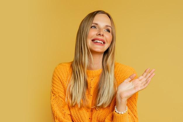 Donna bionda felice in maglione autunnale alla moda arancione che posa sul giallo.