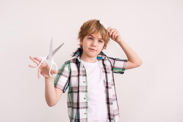 Felice ragazzo biondo aspetto europeo in una camicia bianca che tiene le forbici