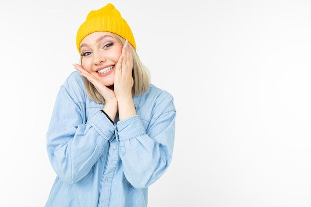 Giovane donna affascinante bionda felice in look casual con camicia di jeans su sfondo bianco.