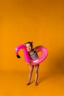 Felice ragazza bionda in un costume da bagno a righe tiene un cerchio gonfiabile rosa con un fenicottero su una superficie gialla con un posto per il testo