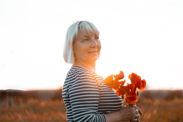 Signora felice della donna dei capelli biondi che tiene il mazzo dei papaveri rossi nel campo al tramonto