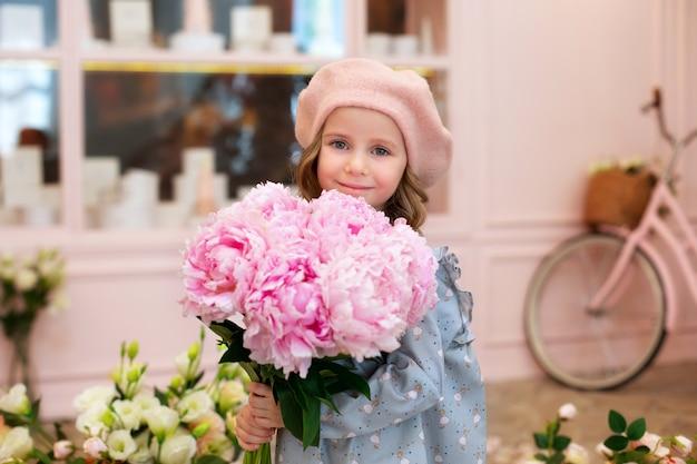 Felice bambina bionda con lunghi capelli ricci e in un berretto con bouquet di peonie rosa.