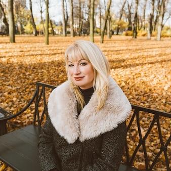 La donna matura bionda felice sta sedendosi sul banco nel parco e nel pensiero di autunno. bella donna
