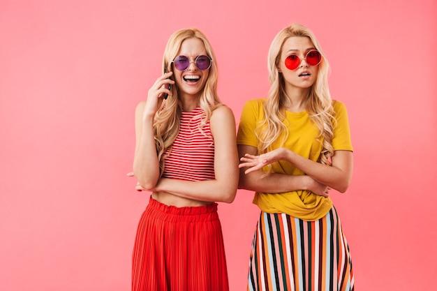 Gemelli biondi felici in occhiali da sole che si divertono insieme mentre uno di loro parla con lo smartphone sul muro rosa