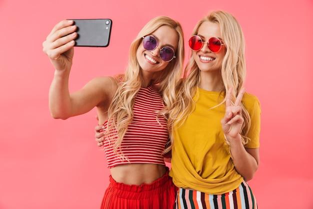 Gemelli biondi felici in occhiali da sole che riposano e fanno selfie sullo smartphone sopra il muro rosa