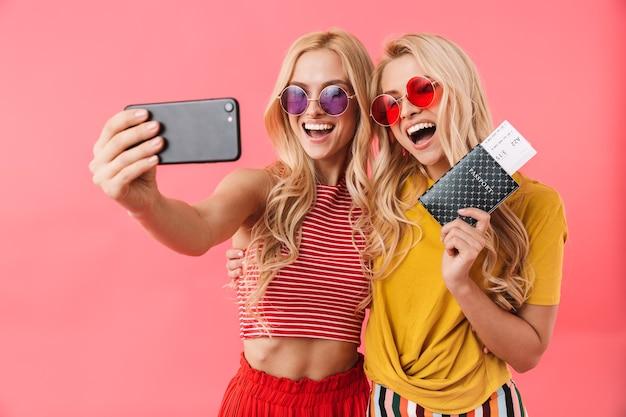 Gemelli biondi felici in occhiali da sole si preparano a inciampare mentre fanno selfie sullo smartphone sul muro rosa