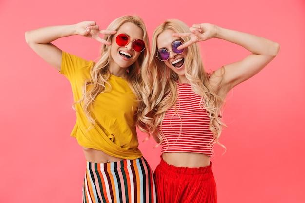Gemelli biondi felici in occhiali da sole che mostrano gesti di pace e guardando la parte anteriore sul muro rosa