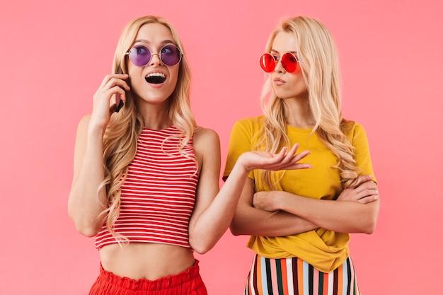 Gemelli biondi felici in occhiali da sole in piedi insieme mentre uno di loro parla tramite smartphone sul muro rosa