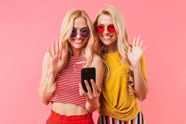 Gemelli biondi felici in occhiali da sole che parlano in videochiamata su smartphone e salutano il muro rosa