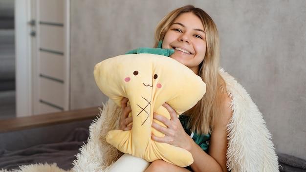 La bionda felice sotto una coperta bianca al mattino abbraccia un cuscino giallo. concetto di mattina felice