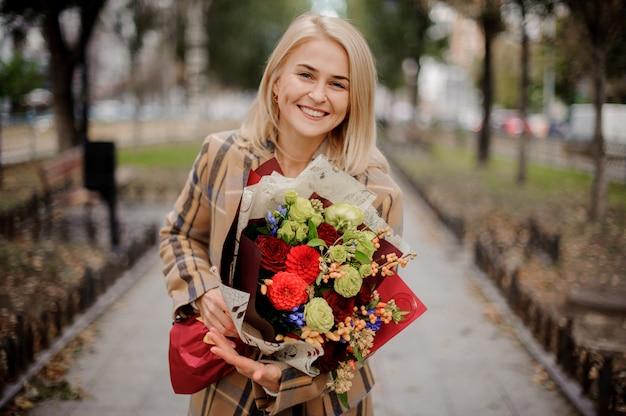 Donna bionda felice in cappotto scozzese che tiene un mazzo luminoso di fiori che cammina sul vicolo