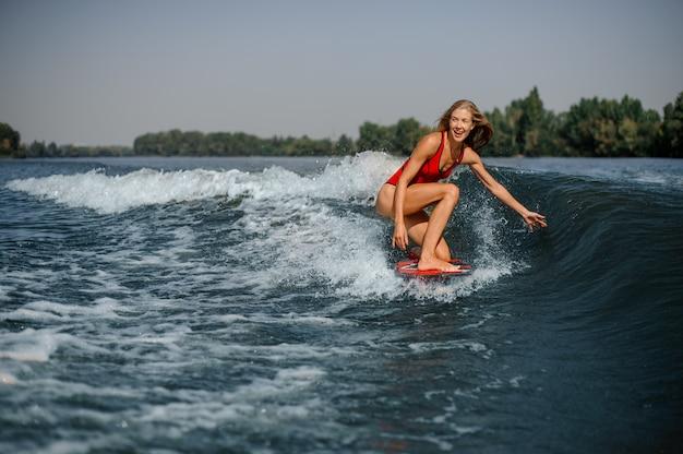 Surfista biondo felice della donna che guida giù l'onda di spruzzatura blu