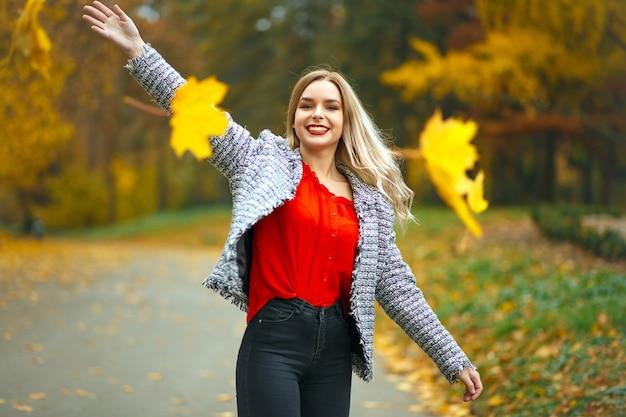 Donna bionda felice con le labbra rosse che spargono foglie gialle nel parco autunnale