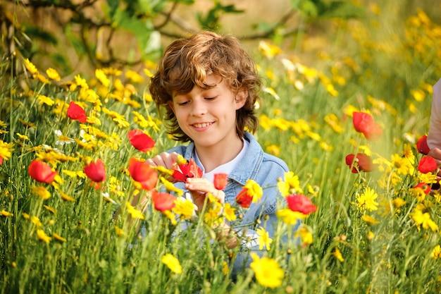 Ragazzo felice che esamina fiore in campo