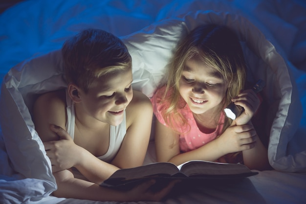 Il ragazzo e la ragazza felici con un libro e una torcia erano al riparo. notte