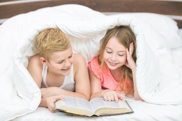 Il ragazzo e la ragazza felici con un libro giacevano sotto il piumone