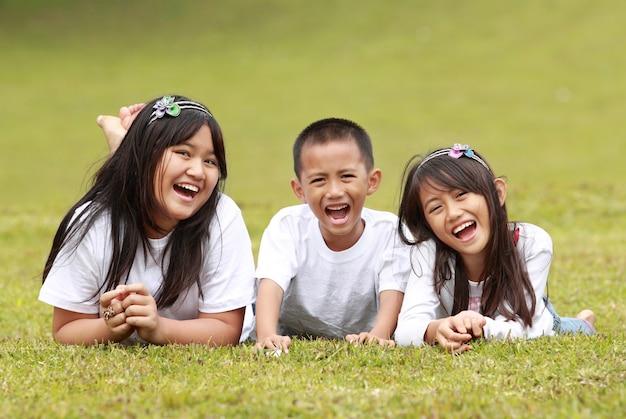 Ragazzo felice e ragazze che si trovano su un'erba verde