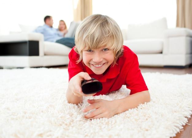 Ragazzo felice che tiene un telecomando che si trova sul pavimento