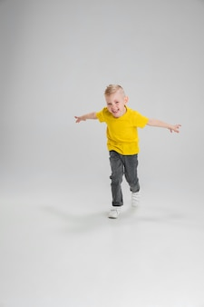 Ragazzo felice isolato sulla parete. sembra felice, allegro. copyspace infanzia, educazione, emozioni, concetto di espressione facciale. saltare in alto, giocare divertendosi