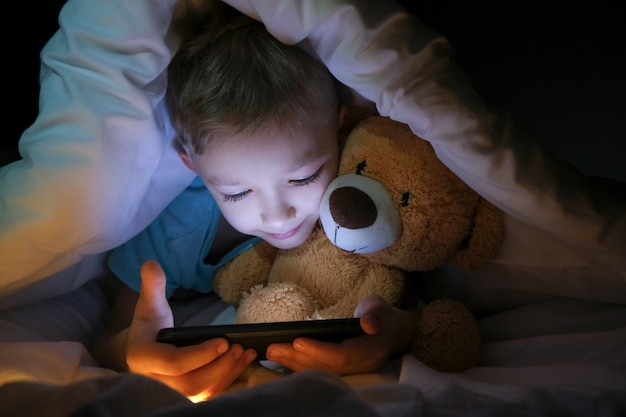 Il ragazzo felice si trova con l'orso del giocattolo nel letto sotto una coperta e utilizzando un dispositivo smartphone tablet digitale al buio. il viso del bambino è illuminato da un monitor luminoso