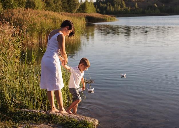 Ragazzo e madre felici vicino al lago Foto Premium