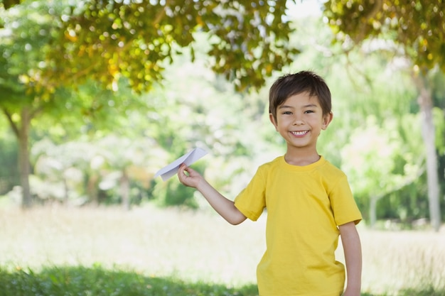 Ragazzo felice che gioca con un aereo di carta al parco