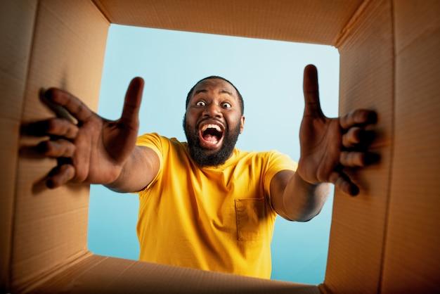 Il ragazzo felice riceve un pacchetto dall'ordine del negozio online. espressione felice e sorpresa