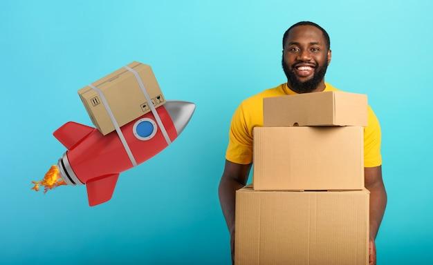 Il ragazzo felice riceve un pacchetto prioritario dal concetto di ordine del negozio online di corriere veloce come un razzo