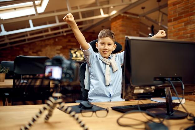 Ragazzo felice che registra vlog, piccolo blogger. blogging per bambini in home studio, social media per un pubblico giovane, trasmissione internet online