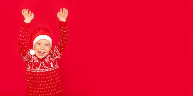 Ragazzo felice su uno sfondo rosso, banner, bambino con le mani in alto