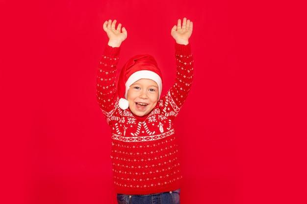 Ragazzo felice su uno sfondo rosso, bambino con le mani in alto
