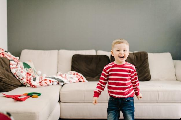 Ragazzo felice in maglioni di babbo natale gioca in casa interna. natale di notte. godersi le vacanze in famiglia. buon natale e felice anno nuovo.