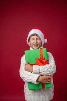 Ragazzo felice con un cappello da babbo natale tiene un regalo di natale e chiude gli occhi su un rosso in studio.
