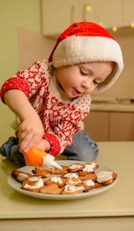 Ragazzo felice in cappelli di santa helper che producono i biscotti. bambino che cucina i biscotti di natale a casa. il bambino prepara il cibo per le vacanze.