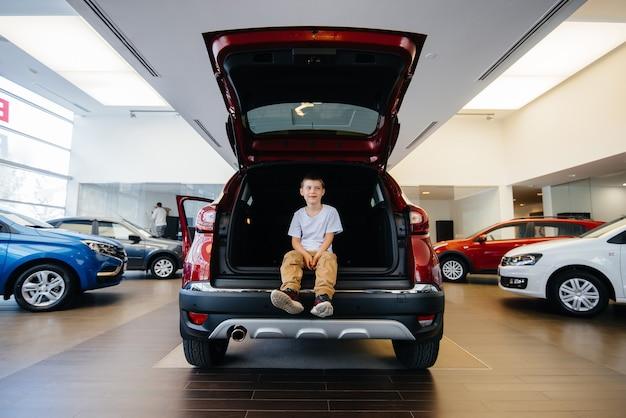 Ragazzo felice che si siede nel bagagliaio di un'auto nuova presso una concessionaria. acquisto di un'auto.
