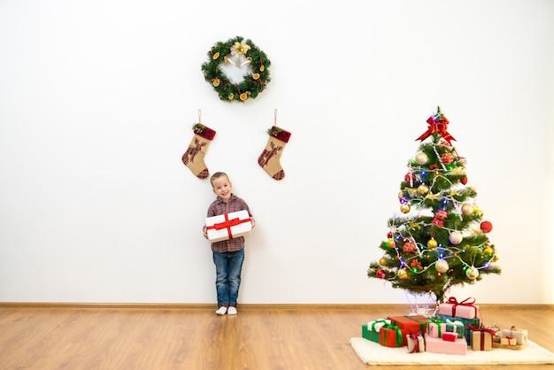 Il ragazzo felice sta vicino all'albero di natale e tiene una scatola regalo