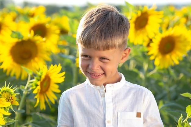Il ragazzo felice sta in un campo di girasoli in fiore