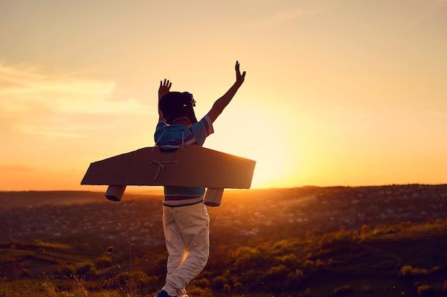 Un ragazzo felice in un costume da supereroe sta giocando con un aeroplano sulla natura al tramonto.