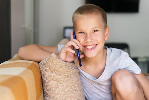 Ragazzo felice che parla al telefono mentre è seduto sul divano di casa in abiti casual ridendo caucas