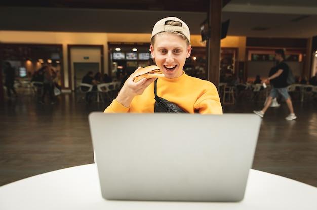 Ragazzo felice con un hamburger in mano, guardando lo schermo del laptop e sorridente