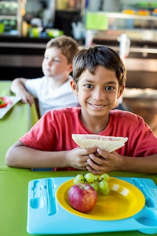 Ragazzo felice con i compagni di classe che hanno pasto
