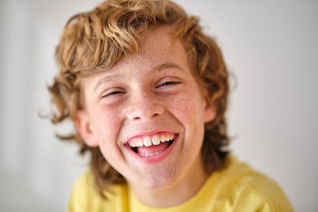 Ragazzo felice con le lentiggini su sfondo chiaro