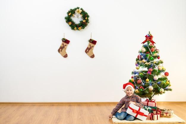 Il ragazzo felice con un regalo si siede vicino all'albero di natale