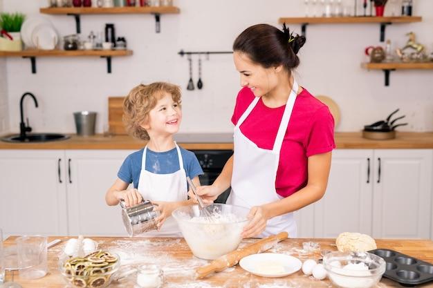 Ragazzo felice con il setaccio guardando sua madre sbattere le uova con la farina nella ciotola mentre parla durante la preparazione del cibo
