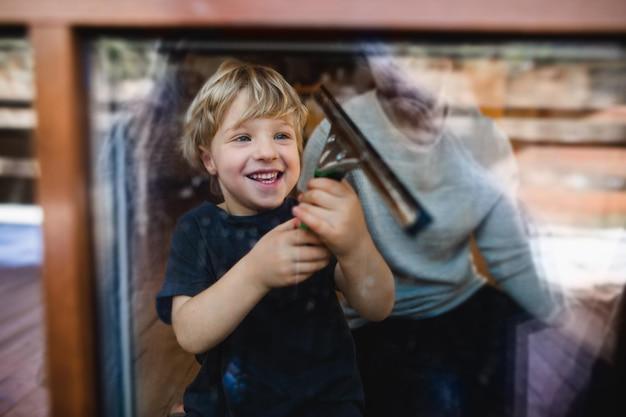 Un ragazzo felice con padre irriconoscibile che pulisce le finestre a casa, concetto di faccende quotidiane.