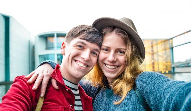 Felice ragazzo e ragazza innamorata che si divertono sinceramente prendendo selfie in area moderna a berlino
