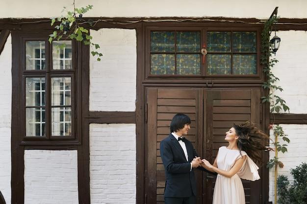 Felice sposa e lo sposo in piedi vicino a vicenda al vecchio sfondo di casa, foto del matrimonio, bella coppia, giorno del matrimonio, ritratto.