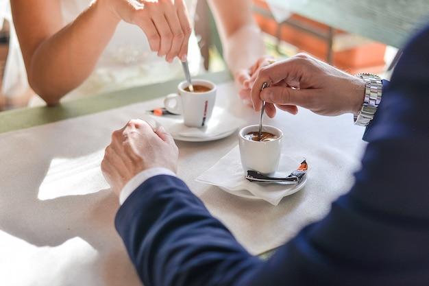 Sposa e sposo felici che si siedono nella caffetteria al tavolo. amare la sposa e lo sposo che bevono caffè al tavolo.