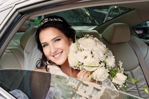 Sposa felice che osserva dal finestrino della macchina