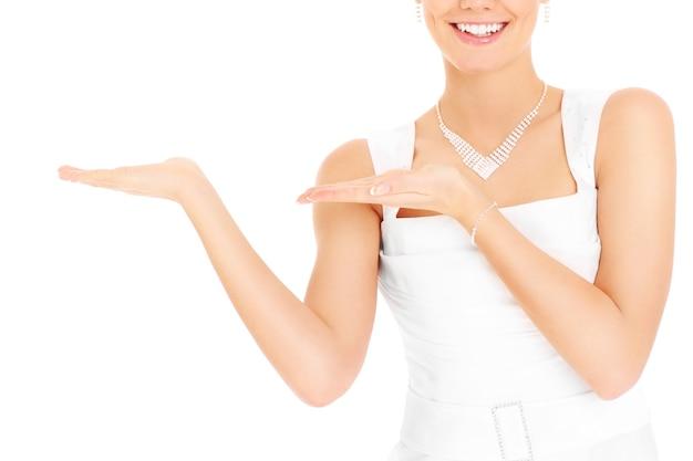 Una sposa felice che mostra qualcosa su sfondo bianco